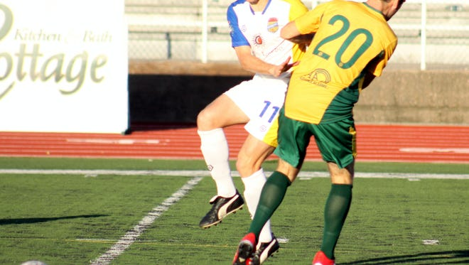 Rafters midfielder Matt Barcelona fights to get past Tulsa's Niall Masterson in the first half of Saturday's 2-0 win.