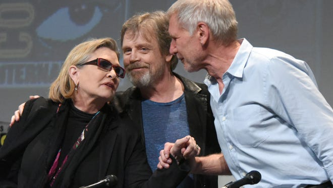 "Carrie Fisher, from left, Mark Hamill, and Harrison Ford attend Lucasfilm's ""Star Wars: The Force Awakens"" panel on day 2 of Comic-Con International in San Diego, Calif., in July."