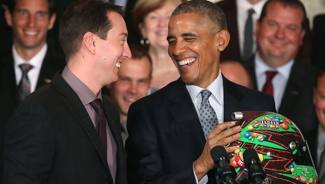 President Barack Obama receives a racing helmet from Sprint Cup champion Kyle Busch during an event in the East Room at the White House.