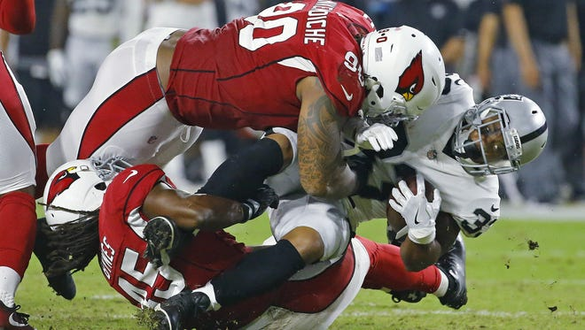 Arizona Cardinals defensive tackle Robert Nkemdiche (90) and Josh Bynes (45) stop Oakland Raiders running back DeAndre Washington (33) in the backfield  in the 2nd  quarter of their NFL game Saturday, Aug. 12, 2017, in Glendale, Ariz.