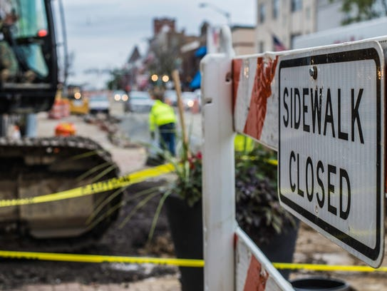 A sidewalk closure sign at the intersection of Eighth