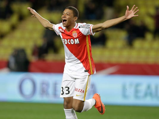 FILE - In this Saturday, Feb. 20, 2016 file photo, Monaco's Kylian Mbappe Lottin celebrates scoring the third goal against Troyes during their French League One soccer match, in Monaco. Because of his electric speed and style of play, the 18-year-old Mbappe has drawn comparisons with Thierry Henry, who is also France's record scorer. (AP Photo/Lionel Cironneau, File)