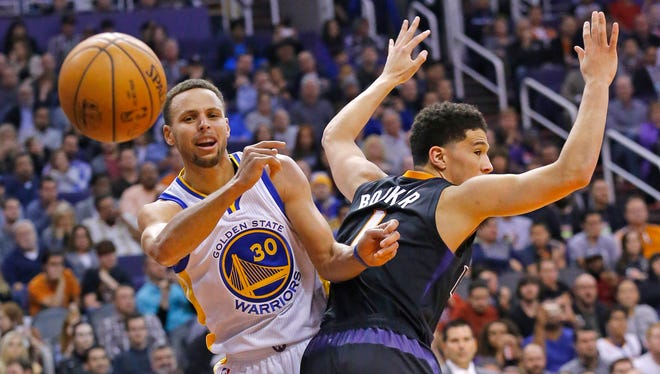 Golden State Warriors guard Stephen Curry (30) makes a pass against Phoenix Suns guard Devin Booker (1) in the second half of their NBA game Friday, Nov. 27, 2015, in Phoenix.