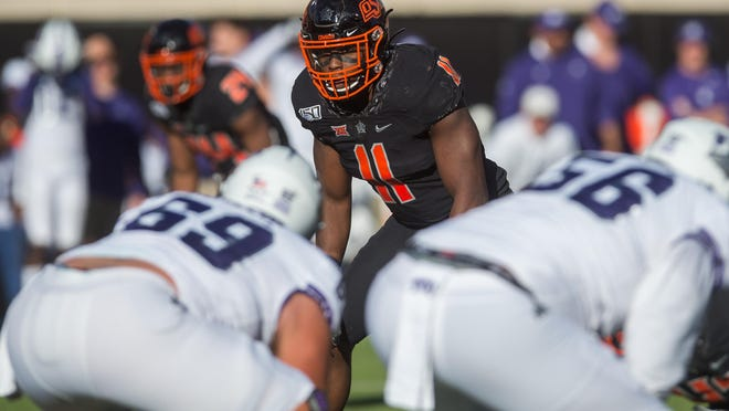 Oklahoma State linebacker Amen Ogbongbemiga looks into the TCU Horned Frogs backfield during a 2019 game. On Tuesday, the senior announced he tested positive for COVID-19.
