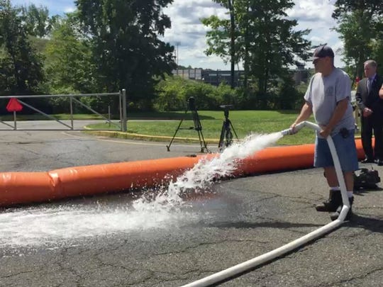 Rockland County employees demonstrate how a new, water-filled barrier can diver potential flood waters.