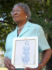 In this Oct. 7, 2010, file photo, Recy Taylor, 90, holds a photo of herself from her days in Abbeville, Ala., outside her home in Winter Haven, Fla.