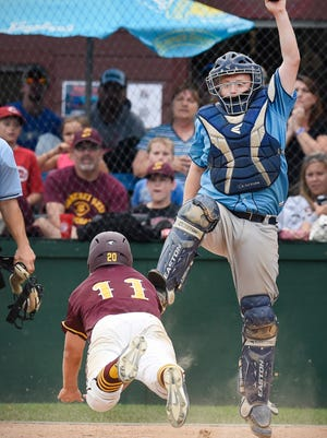 Sobieski's Scott Litchy dives safely to score under the tag by Winsted catcher Matt Wroge during the seventh inning Sunday, Sept. 4, 2016, in Dassel.