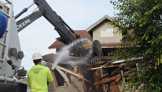 A Ricketts Excavating crew demolishes a house Friday at 523 Zane Ave. The Fairfield County land bank has demolished four homes and raze more in coming weeks.