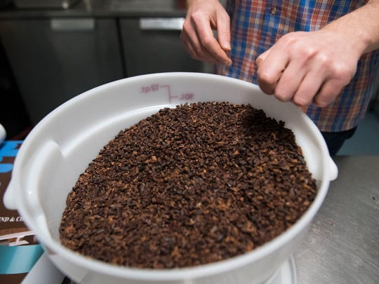 Nathan Hilbert, owner and operator of Unrefined Chocolate, stands next to a bucket of cocoa nibs in North Knoxville on Wednesday, April 25, 2018.