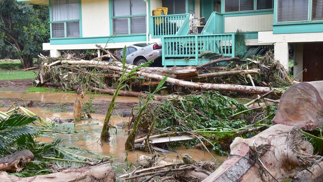 A car is wedged between a house and debris in Anahola, Hawaii, after the Anahola River broke its banks in the pre-dawn hours and flooded the community downstream on April 15, 2018.