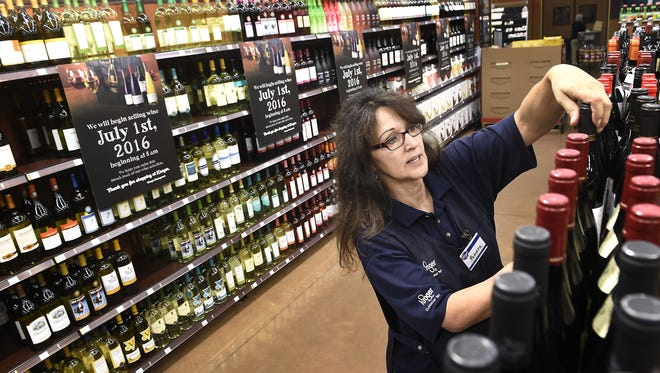 Pamela England straightens the wine section at the Gallatin Kroger that is in place but not open to the public until July 1.