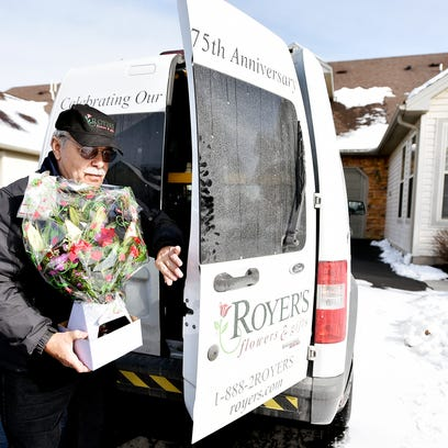 Jim Waughtel carries an order of flowers for delivery