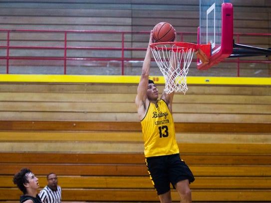 Bettendorf point guard D.J. Carton dunks during a basketball