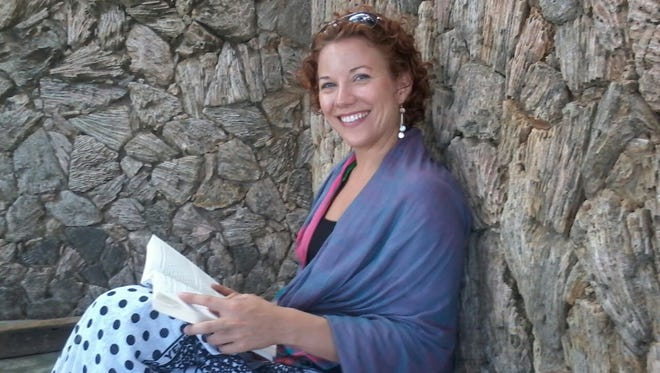 """Amy Crook reads under """"the happy tree"""" in Lamu."""