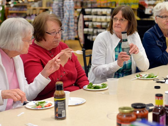 Class participants sample a   no-sugar-added dressing with a strawberry and spinach salad June 23 at Coborn's in Sauk Rapids.