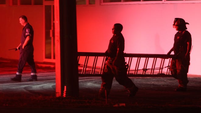 Fort Myers city firefighters take a ladder used by police to search the roof of a building near City of Palms Park back to their truck after a shooting Tuesday evening.