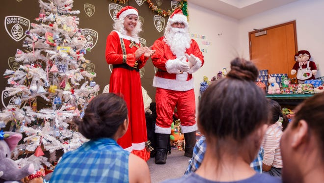 Santa Claus and Mrs. Claus, portrayed by police officers Wil Naval and Jonene Terjale, interact with children attending the Children Smile for Hope Christmas event at the Guam Police Department's precinct in Dededo on Saturday, Dec. 23, 2017. Precinct officers with the law enforcement agency invited underprivileged families in the village to celebrate part of their holiday season at the facility. During the event, children recieved gifts and other goodies donated or collected by the Chasing Rainbows End Organization, Children's Smiles Program, GPD's Mandaña Drug Task Force and other supporters.