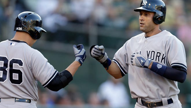 New York Yankees shortstop Derek Jeter (right) is congratulated by teammate Carlos Beltran after scoring against the Oakland Athletics in the first inning Friday. Jeter scored on a sacrifice fly by Mark Teixeira.