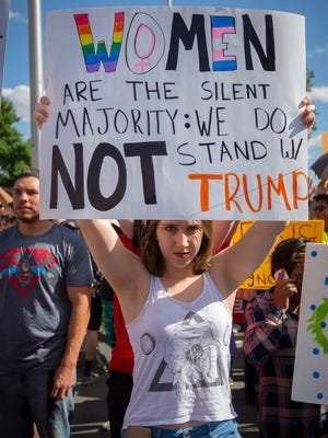 17-year-old Sofia Hoskins holds up a sign outside the Albuquerque Convention Center in Albuquerque, NM, protesting the appearance of presidential candidate Donald Trump at the center, May 24, 2016.