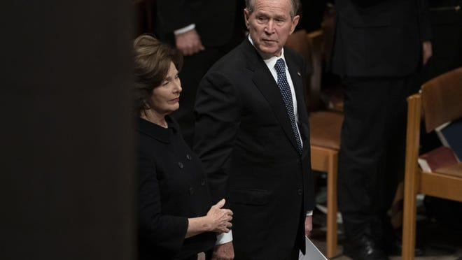 Former President George W. Bush and wife Laura Bush stand together during a State Funeral for former President George H.W. Bush at the National Cathedral,  Dec. 5, 2018, in Washington.