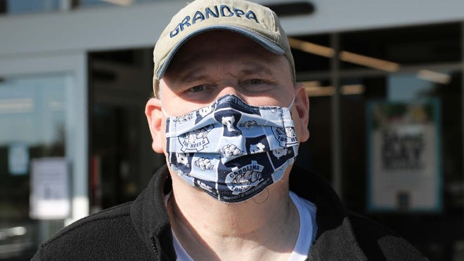 Steve Price wears a University of North Carolina mask in April as he shops at Aldi.