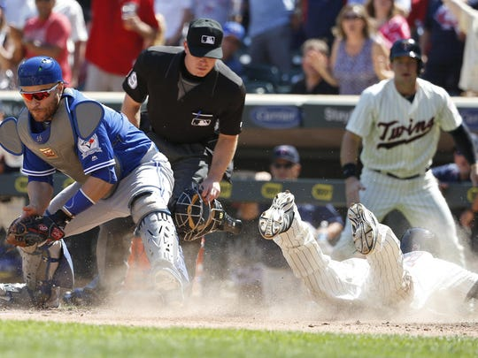 The Minnesota Twins' Darin Mastroianni, right, scores on a double by teammate Danny Santana as Toronto Blue Jays catcher Russell Martin, left, bobbles the throw from right field during the eighth inning Saturday in Minneapolis.