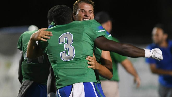 West Florida K Austin Williams (facing camera) is congratulated by teammates after he kicked the winning field goal in Saturday's game against Florida Tech.