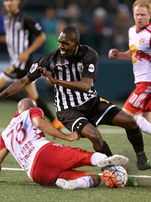 Rhinos Asani Samuels is tackled off the ball by Red Bulls Aurelien Collin  near midfield. The Red Bulls beat the Rhinos 1-0 in the Lamar Hunt U.S. Open Cup match.