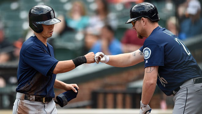 Seattle Mariners' Norichika Aoki, left, is congratulated by Adam Lind after scoring on a single by Nelson Cruz in the first inning of a baseball game against the Baltimore Orioles, Thursday, May 19, 2016, in Baltimore. The Mariners won 7-2.