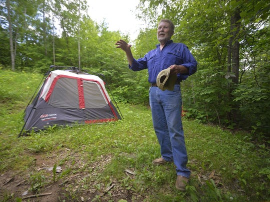 Jim Kubow talks outside his storage tent at Birch Lakes Campground. Among the perks of being a campground host, Kubow gets to plant a small garden at the site.