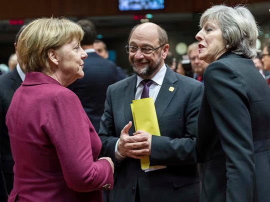 German Chancellor Angela Merkel, left, speaks with British Prime Minister Theresa May, right, and European Parliament President Martin Schulz, center, during a round table meeting at an EU Summit in Brussels on Thursday, Dec. 15, 2016. European Union leaders meet Thursday in Brussels to discuss defense, migration, the conflict in Syria and Britain's plans to leave the bloc.