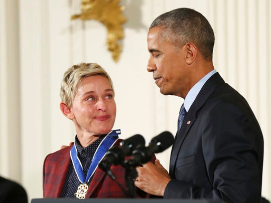 FILE - In this Nov. 22, 2016 file photo, actress, comedian, and talk show host Ellen DeGeneres, glances at President Barack Obama as she is presented the Presidential Medal of Freedom during a ceremony in the East Room of the White House in Washington. DeGeneres made history 20 years ago as the first prime-time lead on network TV to come out, capturing the hearts of supporters gay and straight amid a swirl of hate mail, death threats and, ultimately, dark times on and off the screen.