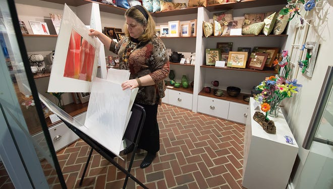 Tamora Kowalski working at her job at the Biggs Museum of American Art in Dover on Friday Nov.14, 2014 while her husband Jake is at the Dover Public Library studying for his certified public accountants test.  They drive up to Dover from Bishopville, MD.