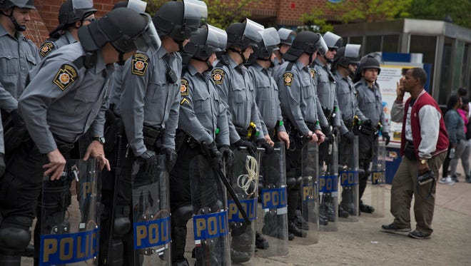 Police and National Guard mobilize in riot gear at Pennsylvania Avenue and W. North Avenue in Baltimore.