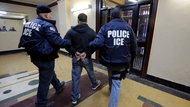 Immigration and Customs Enforcement officers escort a man in an apartment building in the Bronx borough of New York during a series of raids on March 3, 2015.