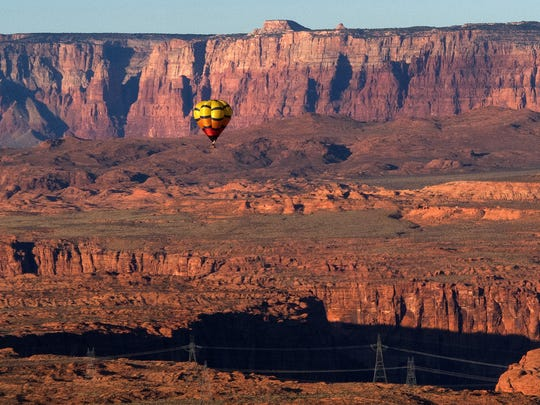 A hot air balloon participating in the 13th annual Page Lake Powell Hot Air Balloon Regatta floats in the skies above Page with red sandstone cliffs and the southern end of Glen Canyon in the background Sunday, Nov. 8, 2015. A weekend filled with fantastic ballooning weather saw 60 hot air balloons filling the skies over Lake Powell on Friday, Saturday and Sunday mornings. In additions, about 20 of the balloons were lined up along Lake Powell Boulevard Saturday night for a balloon glow and street festival.