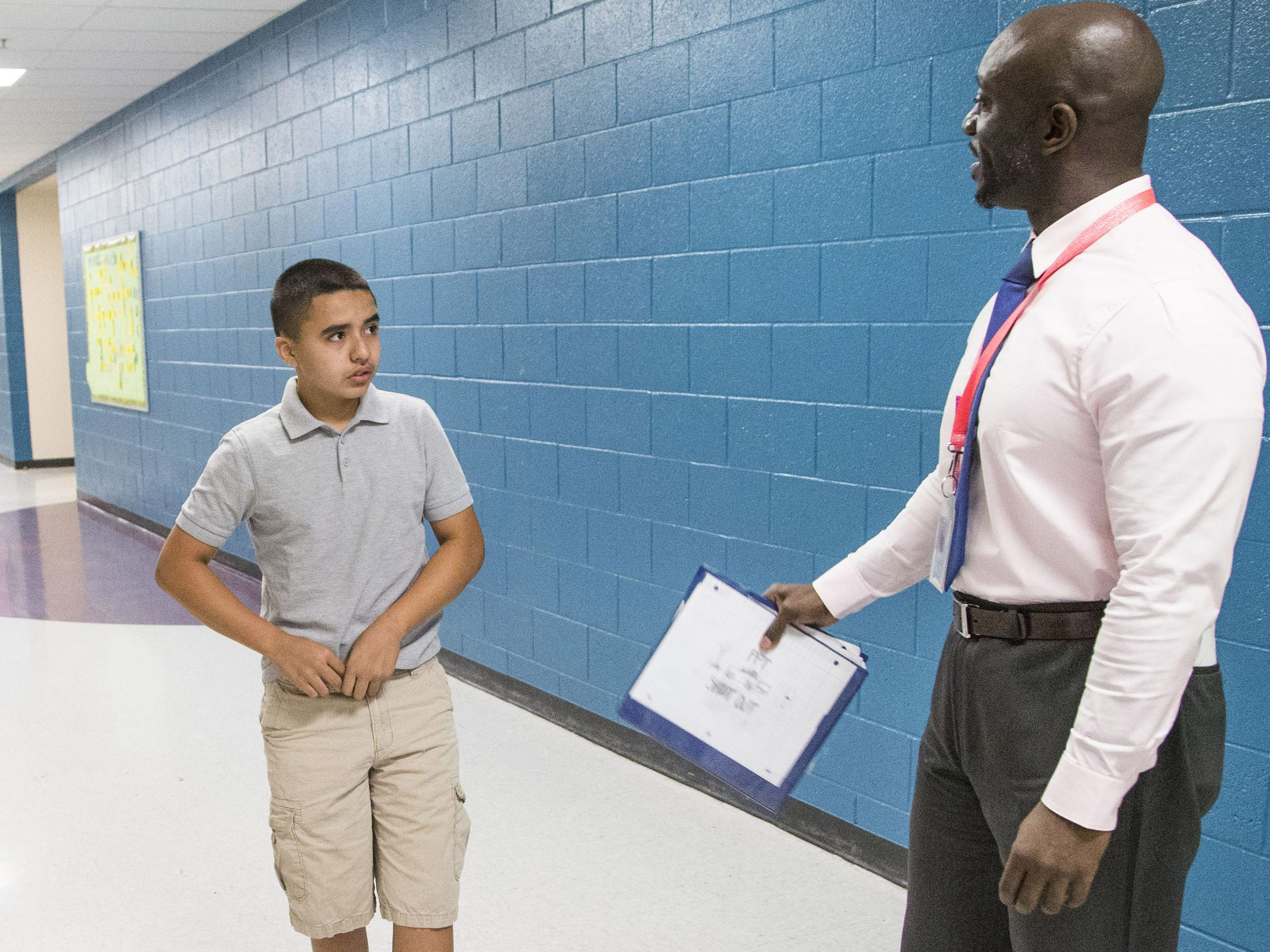 """Principal Eric Atuahene reminds student Alex Mata Cevas to tuck his shirt in before the start of the school at Quentin Elementary. """"Now you are ready to learn,"""" Atuahene tells Alex."""
