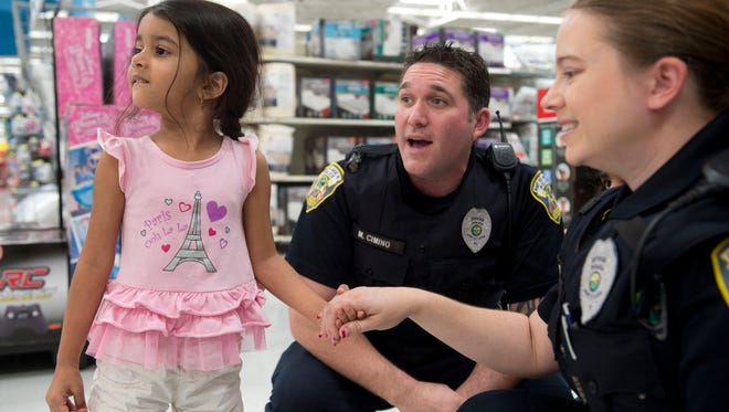 Jada Moore, 4, of Port St. Lucie, surveys the Wal-Mart toy department with Port St. Lucie Police Officers Michael Cimino (center) and Ariel Dennis during the department's annual Shop with a Cop event on Wednesday, Dec. 14, 2016 at the Wal-Mart in Port St. Lucie. Dozens of officers paired up with the Boys & Girls Clubs of St. Lucie County to take children on $100 shopping sprees with gift cards provided by Wal-Mart and from donations to the police department.