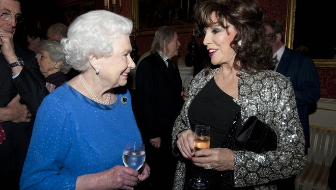 Queen Elizabeth II talks to Joan Collins at reception at Buckingham Palace on in February 17. Collins was named a dame in queen's New Year's honors list on Dec. 30.
