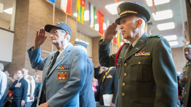 Guest speakers and Korean War Veterans (L to R) Army Staff Sgt. Stanley Levin and Army Capt. A.T. Jackson salute during the 2015 Veterans Day Celebration at Rowan College at Gloucester County. Wednesday, November 11, 2015.