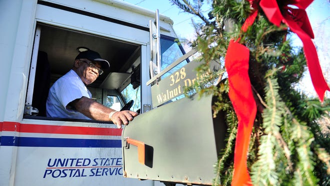"""Richard """"Mac"""" McDonald runs his mail route Wednesday on Walnut Drive. He's been driving the Belle Meade route nearly every day for 28 years. McDonald was honored earlier this month for 50 years of government service, including 46 with the United States Postal Service."""
