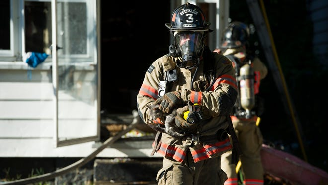 Evansville Fire Lt. Adam Brock rescues a cat named Cheetah from house fire located at 2115 W. Columbia Street, Monday, Sept. 12, 2016. Five people, two cats, a rabbit and a dog were displaced in the fire and one person was taken to the hospital.