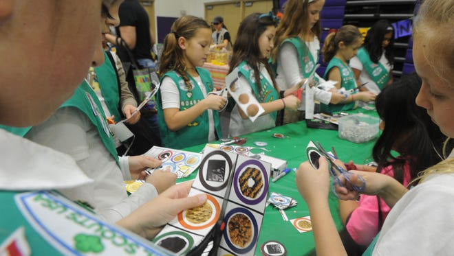 Addison Breton (left), of Girl Scout Troop 60491 in Simi Valley, cuts paper cookies at the Girl Scouts of California's Central Coast sales training meet-up at California Lutheran University.