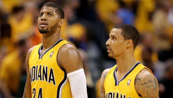 Indiana Pacers forward Paul George and guard George Hill walk off the court against the Atlanta Hawks in the first round of the NBA Eastern Conference playoffs Saturday, April 19, 2014, at Banker Life Fieldhouse.