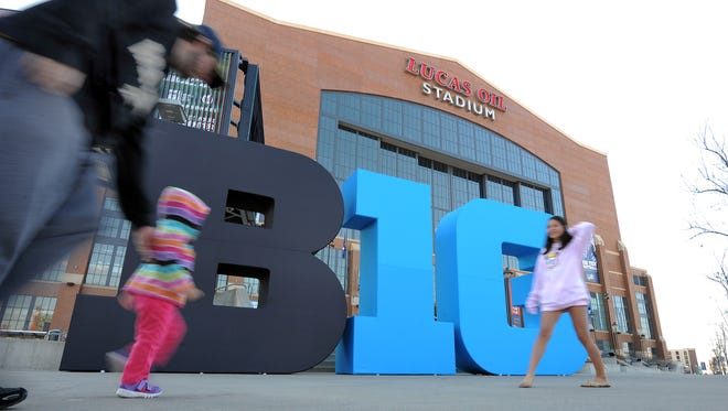 FILE - Big Ten football fans walk by the Big Ten logo out front of Lucas Oil Stadium Nov. 30, 2012 in preparation for this the Big Ten football championship game.
