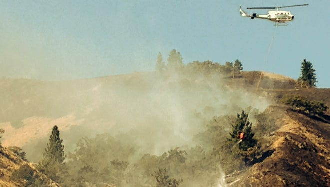 A helicopter drops water from a bucket on the Rowena fire, Wednesday, Aug. 6, 2014, about seven miles west of The Dalles, Ore.