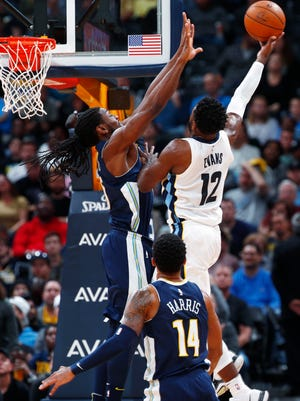 Denver Nuggets forward Kenneth Faried, left, goes up to block a shot by Memphis Grizzlies guard Tyreke Evans as Nuggets guard Gary Harris, front, trails the play during the second half of an NBA basketball game Friday, Nov. 24, 2017, in Denver. The Nuggets won 104-92. (AP Photo/David Zalubowski)