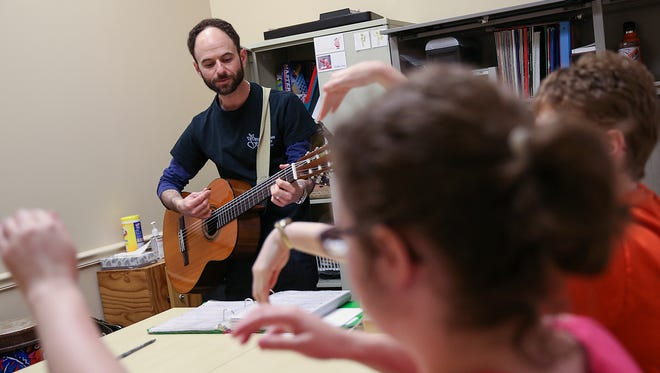 """Andy Panayides, the director of music therapy, leads a session as clients dance along to the tune of """"Surfing U.S.A."""" at Opportunities for Positive Growth, in Fishers, Ind."""