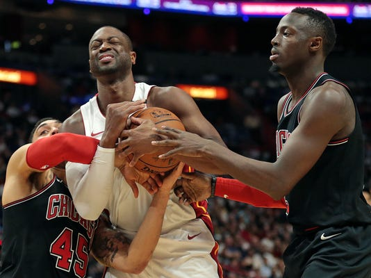Miami Heat guard Dwyane Wade, center, battles for the ball with Chicago Bulls forward Denzel Valentine (45) and guard Jerian Grant, right, during the second half of an NBA basketball game Thursday, March 29, 2018, in Miami. (AP Photo/Joel Auerbach)