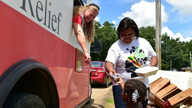 American Red Cross member Michelle Wilson, left, hands food out to residents in Crosby, Miss. where historic flooding damaged many homes.
